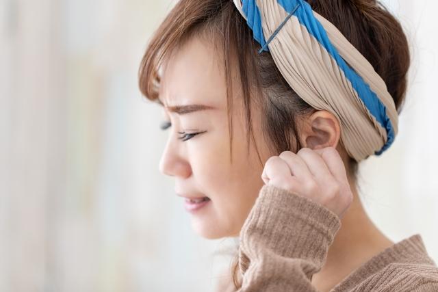 耳の痛み・耳を押さえる女性