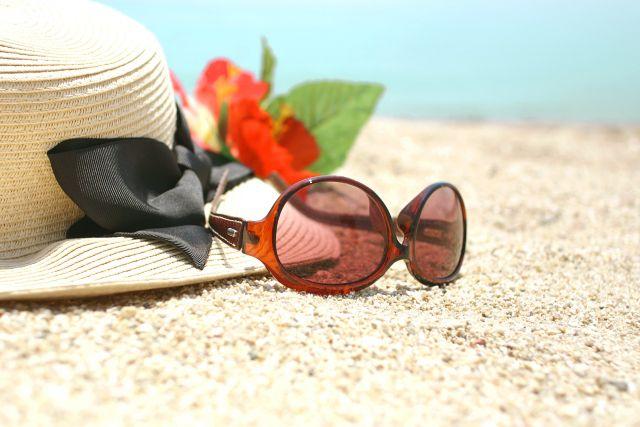 砂浜に置かれた帽子とサングラスのイメージ
